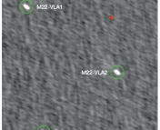 VLA radio continuum image of the core of M22. The two bright circled objects, M22-VLA1 and M22-VLA2, are the sources identified as stellar-mass black holes. The red cross denotes the photometric cluster center.