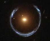 A horseshoe-shaped image behind a single red galaxy.  Photo credit ESA/Hubble and NASA.