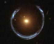 A horseshoe-shaped image behind a single red galaxy.  Photo credit ESA/Hubble and NASA.