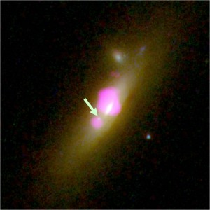 Hubble (background) and Chandra (purple) image of SDSS J1126+2944. The arrow marks the second black hole. (From http://casa.colorado.edu/~comerford/press)