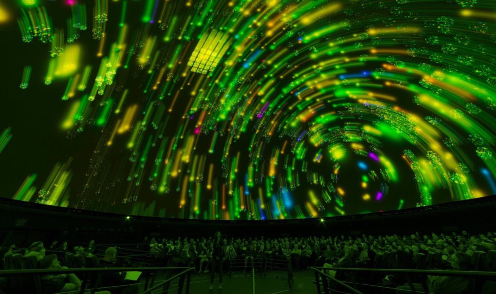 Green star trails track across the dome in a planetarium will a full audience.