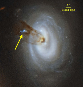 Close-up image of a blue spiral galaxy. In the top-right is a scale, showing that the galaxy is approximately 4 kpc across and 6 kpc in height. Streams of dark orange gas can be seen coming from the centre of the galaxy, and moving towards the top-left of the image. The gas is clumpy, not a smooth cloud. A bright blue patch can be seen in the gas, with a yellow arrow pointing towards it.