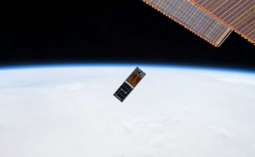 Photograph from the ISS showing two cubesats being deployed into orbit with Earth visible below.