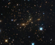 This NASA/ESA Hubble Space Telescope image shows a massive galaxy cluster glowing brightly in the darkness.