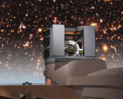 Artist's conception of the Vera Rubin observatory with the night sky above filled with a simulated image of what an image from the observatory will look like. The telescope is peeking out of two rectangular shutters, and the entire structure is massive compared to a few cars down at the base of the building.