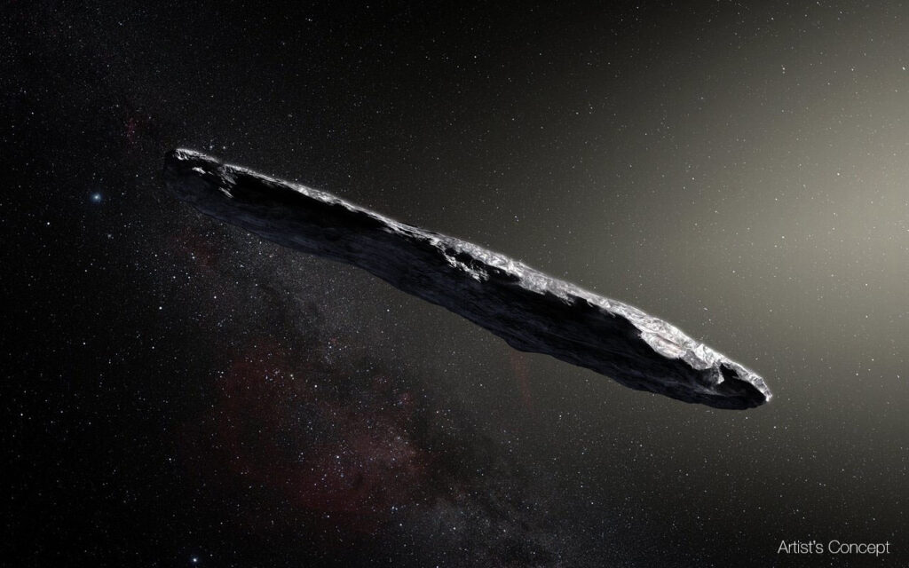 A highly elongated rock-looking object is floating in space. Behind it, hundreds of distant stars can be seen, as well as light from nebulae and clouds of dust. This is an artist's rendition of Oumuamua, the first interstellar object ever discovered.