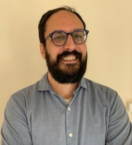 Image of Dr. Enrique López Rodríguez in front of a cream-colored background. He is a white Spanish man with short-ish hair and a beard and round black glasses, smiling widely at the camera.
