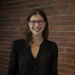 Image of Dr. Jenny Bergner, a brunette white woman with long straight hair and glasses, smiling in front of a brick wall.