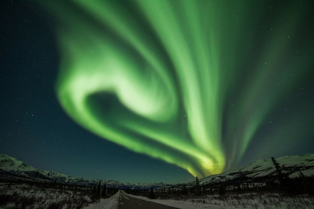 Curtains of green light hang in the sky above a snowy Alaskan landscape