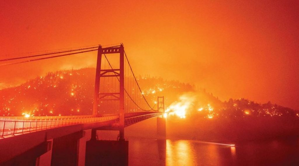 An eerie scene of the Golden Gate Bridge, with an orange sky backdrop, with raging fires in the background due to the California Wildfires.