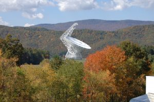 The Green Bank Telescope in daylight, pointed toward the sky, surrounded by trees with autunm-colored leaves