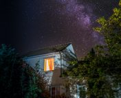Image of a house with a view of a single window with the light on. In the background the Milky Way galaxy is visible