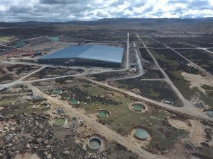 Aerial photo of the LHAASO experiment showing a large rectangular structure surrounded by many small cylindrical tanks