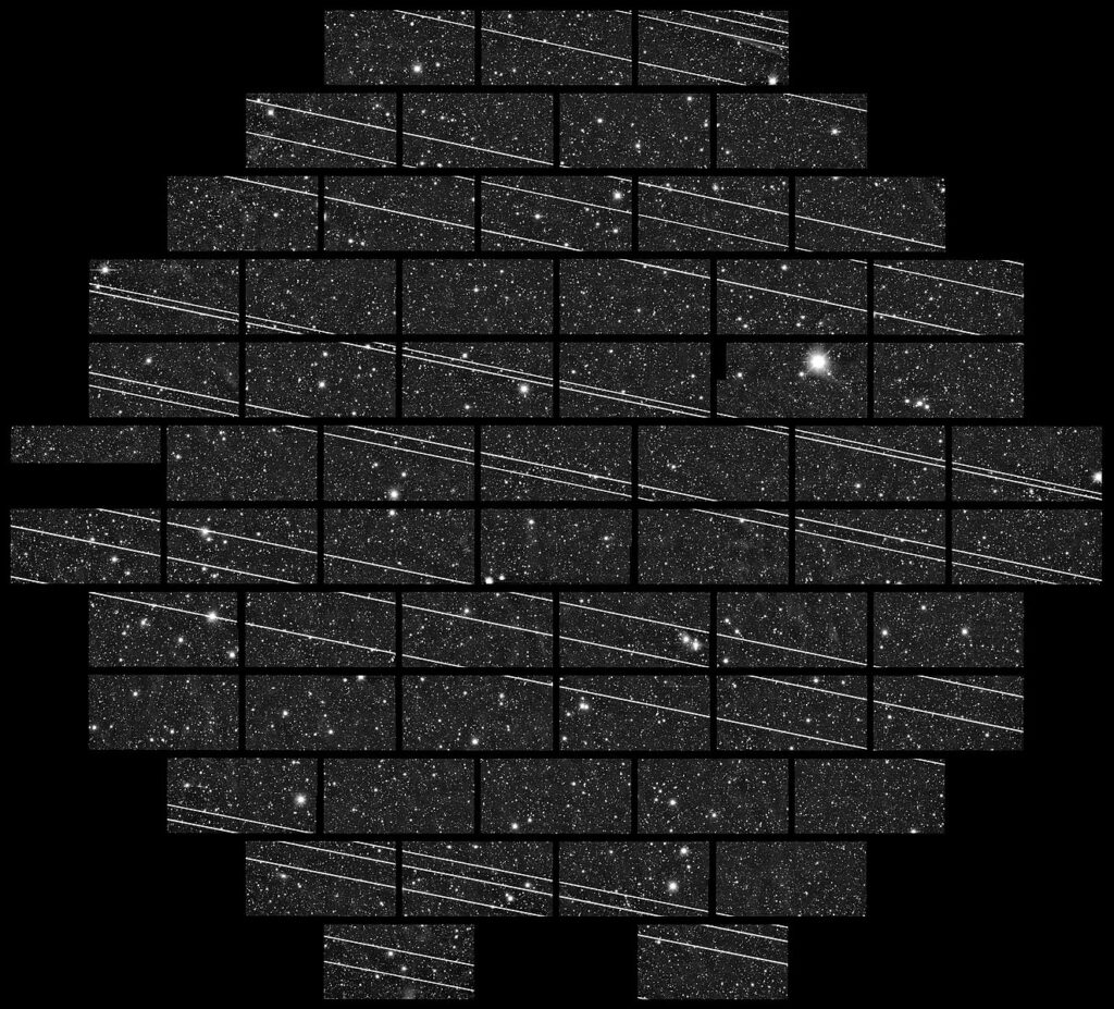 Science image of the sky showing a grid of tiled images, each with stars/galaxies in the background and streaks of light in the foreground covering the astronomical objects.